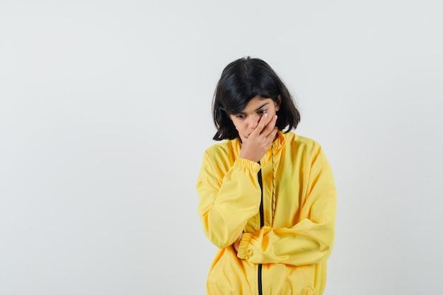 Mała dziewczynka trzyma rękę na ustach w żółtej bluzie z kapturem i wygląda niezdecydowany. przedni widok.