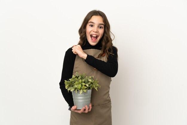 Mała dziewczynka trzyma roślinę na białym tle na białej ścianie świętuje zwycięstwo
