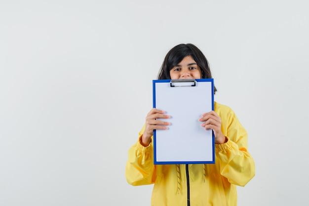 Mała dziewczynka trzyma schowek w żółtej bluzie z kapturem i szuka zadowolony. przedni widok.