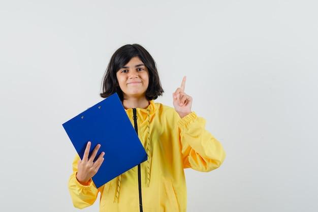 Mała dziewczynka trzyma schowek, wskazując w żółtą bluzę z kapturem i patrząc wesoło. przedni widok.