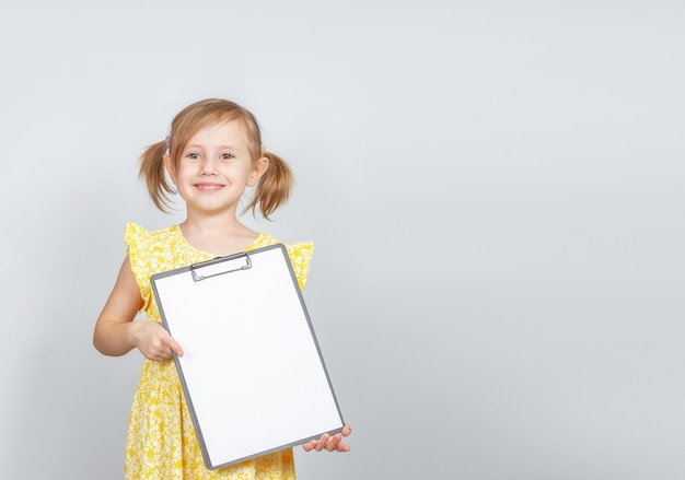 Mała dziewczynka trzyma schowek z czystym papierem