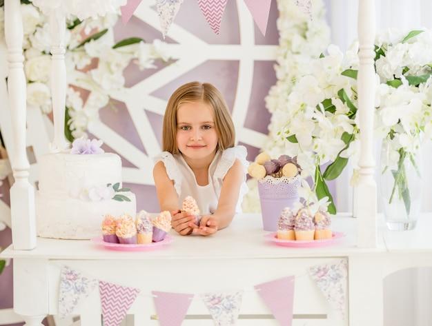Mała dziewczynka trzyma słodkiego tort w cukierku barze