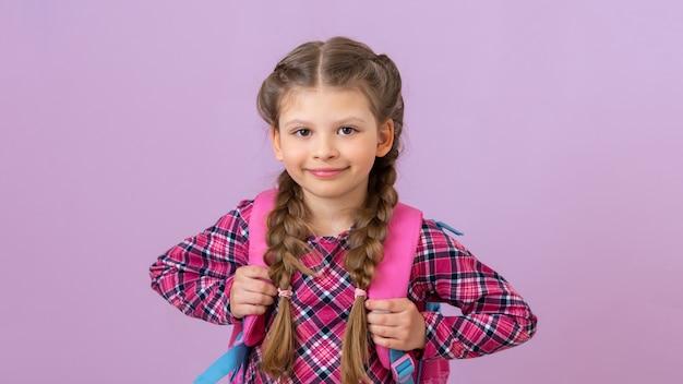 Mała dziewczynka trzyma szkolną tornister i uśmiecha się na różowym tle.