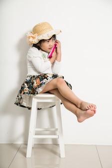 Mała dziewczynka trzyma telefon do rozmowy przez telefon z przyjaciółką.