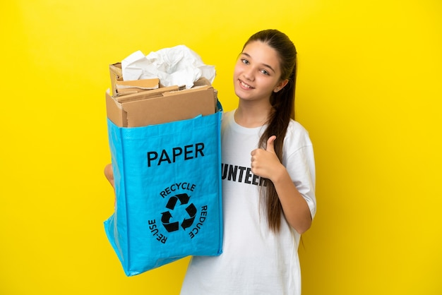 Mała dziewczynka trzyma torbę do recyklingu pełną papieru do recyklingu na izolowanym żółtym tle, pokazując gest kciuka w górę