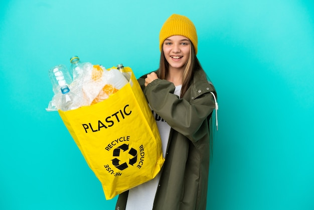 Mała dziewczynka trzyma torbę pełną plastikowych butelek do recyklingu na odosobnionym niebieskim tle świętującym zwycięstwo