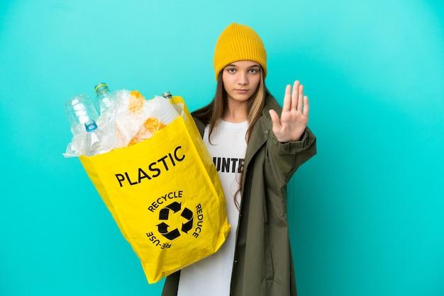 Mała dziewczynka trzyma torbę pełną plastikowych butelek do recyklingu na odosobnionym niebieskim tle, wykonując gest zatrzymania
