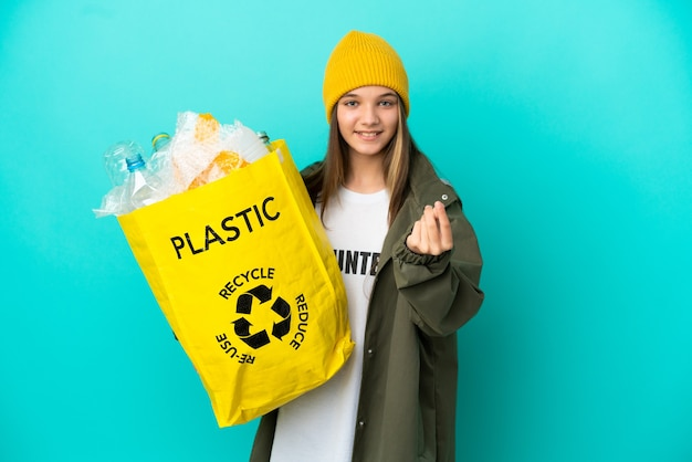 Mała dziewczynka trzyma torbę pełną plastikowych butelek do recyklingu na odosobnionym niebieskim tle zarabiania pieniędzy