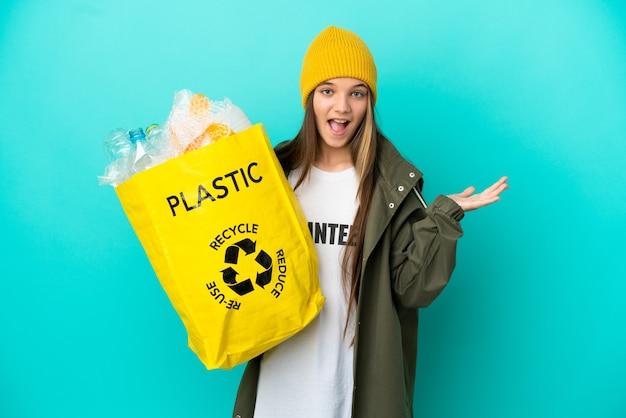 Mała dziewczynka trzyma torbę pełną plastikowych butelek do recyklingu na odosobnionym niebieskim tle ze zszokowanym wyrazem twarzy