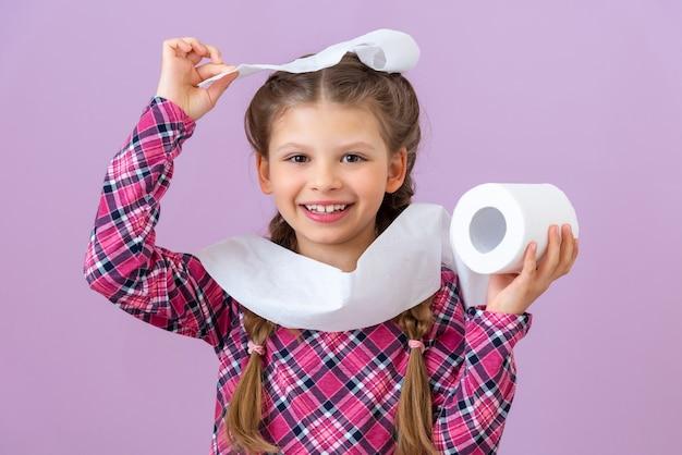Mała dziewczynka trzyma w dłoni papier toaletowy i uśmiecha się na fioletowym tle