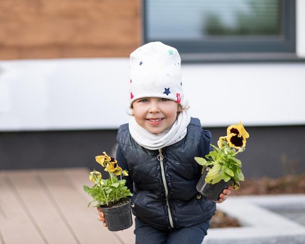 Mała dziewczynka trzyma w dłoniach kwiaty bratek, asystent matki.