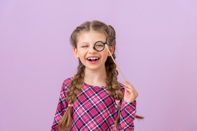 Mała dziewczynka trzyma w pobliżu twarzy parę przemyślnych okularów.