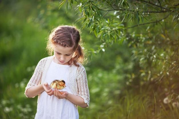 Mała dziewczynka trzyma w rękach słodkie kaczątko.