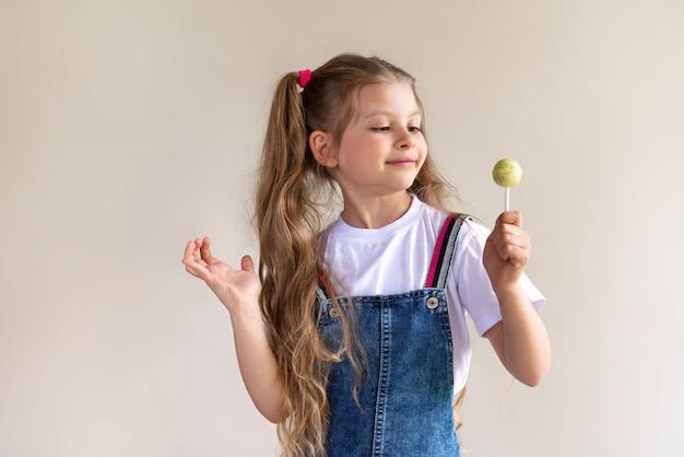 Mała dziewczynka trzyma w rękach żółtego lizaka.