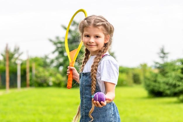 Mała dziewczynka trzyma w ręku rakietę tenisową.