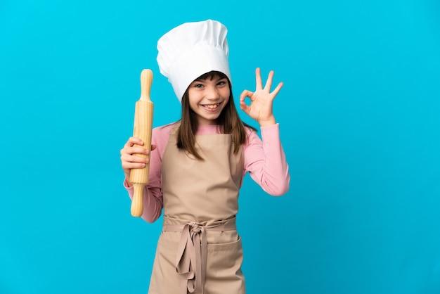 Mała dziewczynka trzyma wałek do ciasta na białym tle na niebieskim tle wyświetlono znak ok palcami