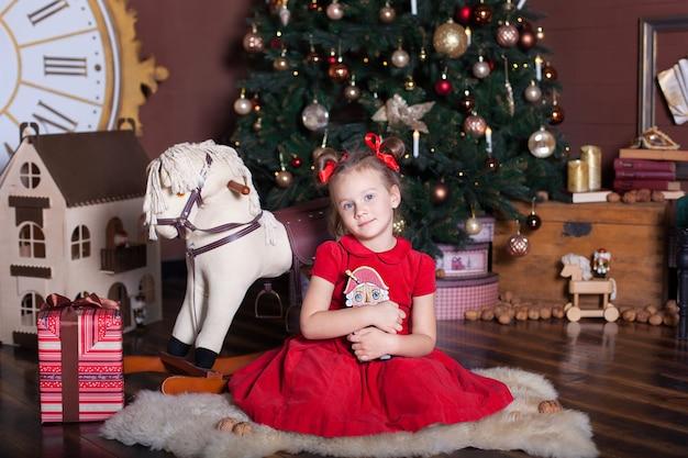 Mała dziewczynka trzyma zabawkę dziadek do orzechów w pobliżu choinki i prezent