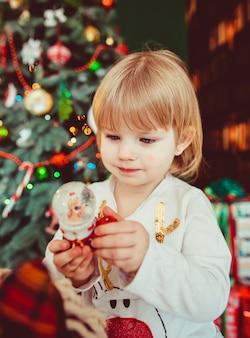 Mała dziewczynka trzyma zabawkę i stoi w pobliżu choinki