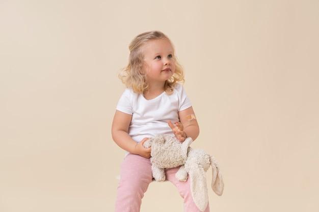 Mała dziewczynka trzyma zabawkę po otrzymaniu szczepionki