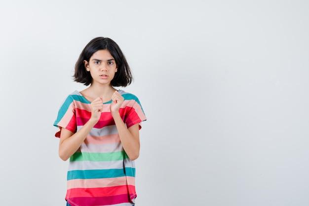 Mała dziewczynka trzyma zaciśnięte pięści w koszulce i wygląda na sfrustrowaną. przedni widok.
