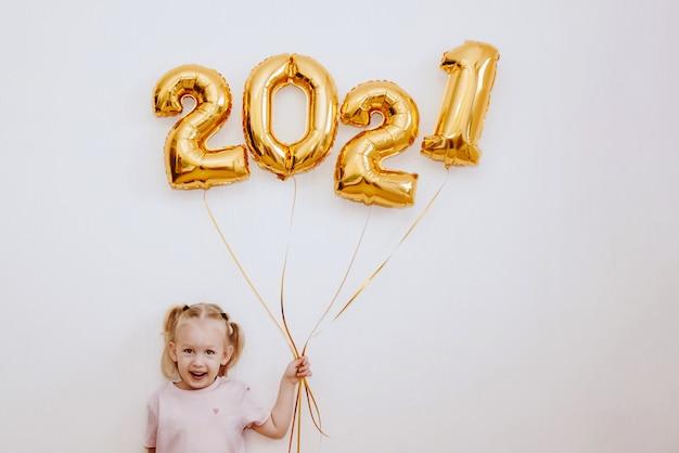 Mała dziewczynka trzyma złote balony ze złotymi numerami