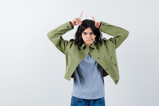 Mała dziewczynka trzymając palce nad głową jak rogi w płaszczu, koszulce, dżinsach i śmiesznie wyglądający. przedni widok.