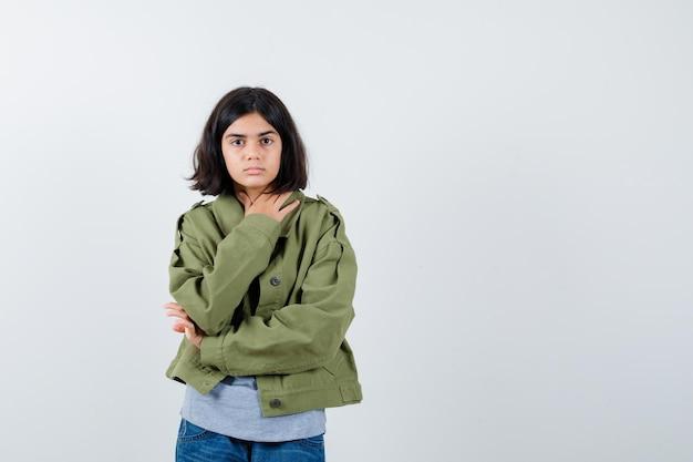 Mała dziewczynka trzymając rękę na klatce piersiowej w płaszcz, t-shirt, dżinsy i pewny siebie. przedni widok.