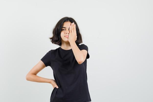 Mała dziewczynka trzymając rękę na oku w czarnej koszulce, widok z przodu.