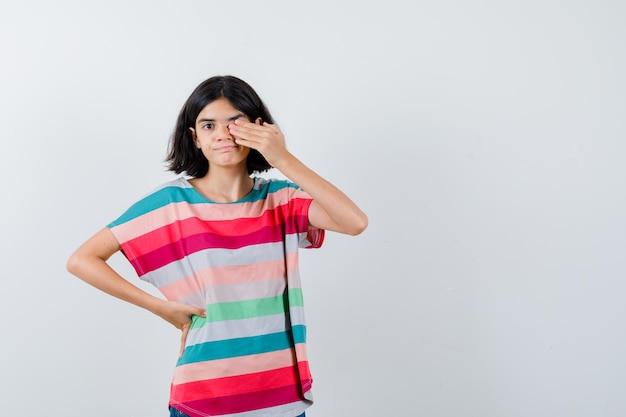Mała dziewczynka trzymając rękę na oku w koszulce i patrząc beznadziejnie, widok z przodu.