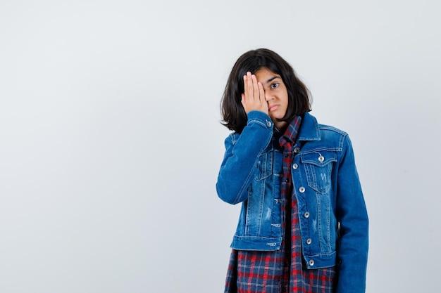 Mała dziewczynka trzymając rękę na oku w koszuli, kurtce i patrząc zamyślony, widok z przodu.