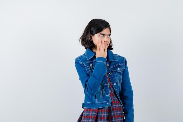 Mała dziewczynka trzymając rękę na policzku w koszuli, kurtce i patrząc zamyślony, widok z przodu.
