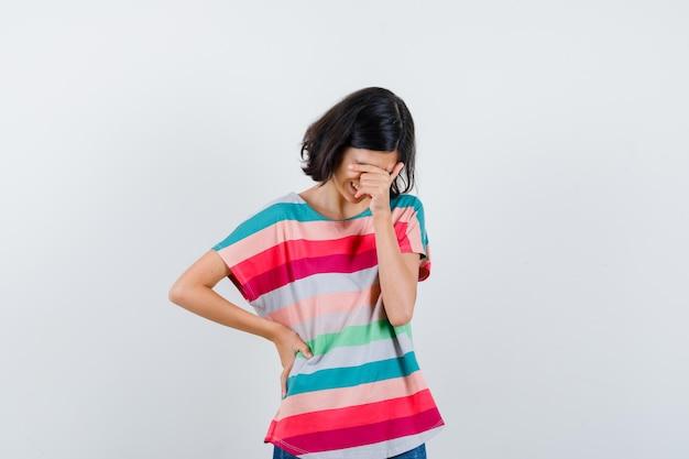 Mała dziewczynka trzymając rękę na twarzy w t-shirt i patrząc wesoło, widok z przodu.