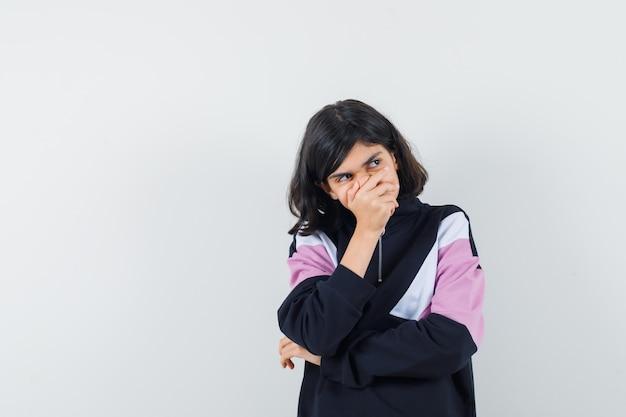 Mała dziewczynka trzymając rękę na ustach w koszuli i patrząc zamyślony, widok z przodu.