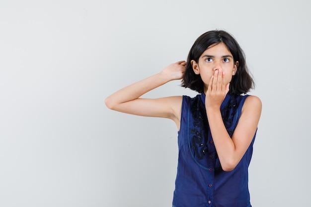 Mała dziewczynka trzymając rękę na ustach w niebieskiej bluzce i patrząc zaskoczony, widok z przodu.