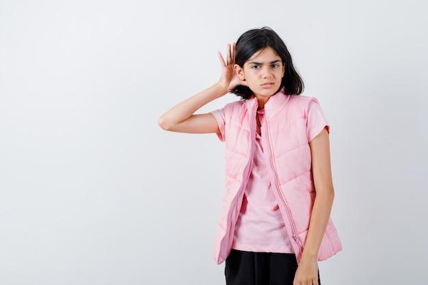Mała dziewczynka trzymając rękę za uchem