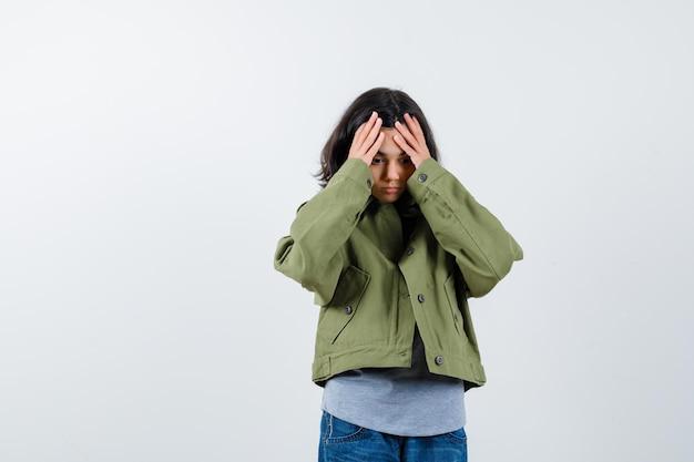 Mała dziewczynka trzymając się za ręce na czole w płaszcz, t-shirt, dżinsy i patrząc zapominalski, widok z przodu.
