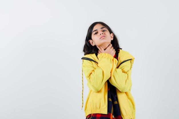 Mała dziewczynka trzymając się za ręce na gardle w kraciastej koszuli, kurtce i patrząc źle, widok z przodu.