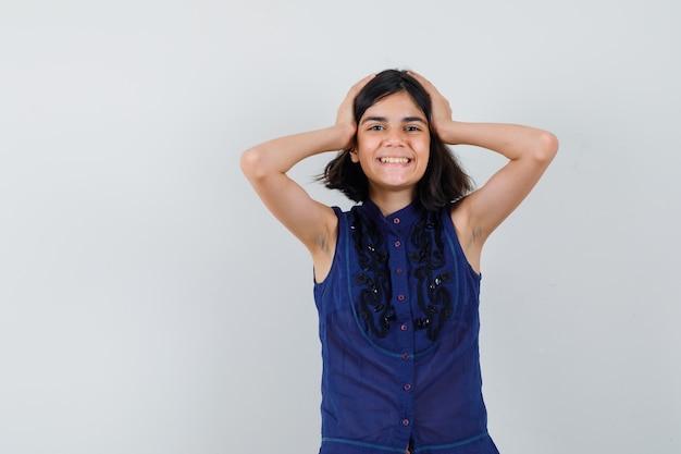 Mała dziewczynka trzymając się za ręce na głowie w niebieskiej bluzce i patrząc szczęśliwy. przedni widok.