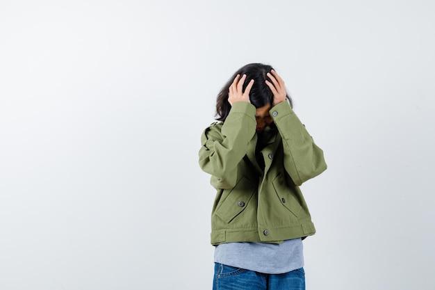 Mała dziewczynka trzymając się za ręce na głowie w płaszcz, t-shirt, dżinsy i patrząc zirytowany, widok z przodu.