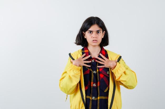 Mała dziewczynka trzymając się za ręce na piersi w kraciastej koszuli, kurtce i patrząc poważnie