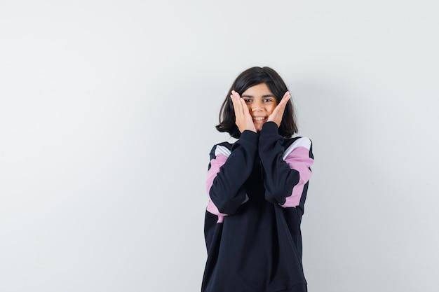 Mała dziewczynka trzymając się za ręce na policzkach w koszuli i patrząc szczęśliwy. przedni widok.