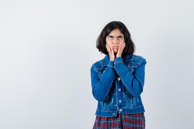 Mała dziewczynka trzymając się za ręce na policzkach w koszuli, kurtce i niezdecydowany. przedni widok.