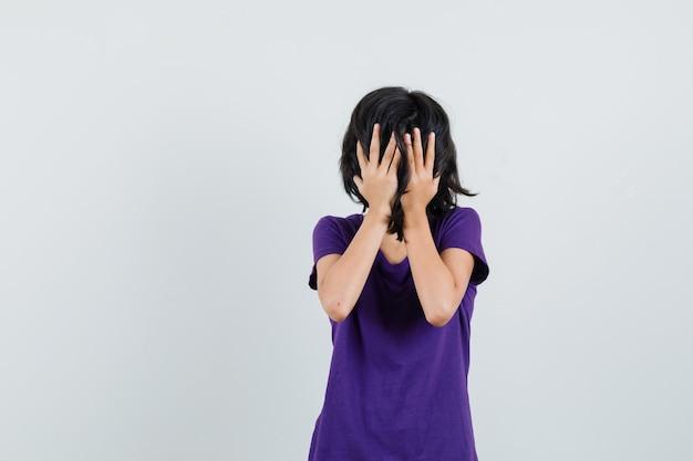 Mała dziewczynka trzymając się za ręce na twarzy w t-shirt i patrząc przestraszony.