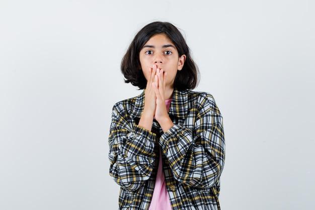 Mała dziewczynka trzymając się za ręce na ustach w koszuli, kurtce i patrząc przerażony. przedni widok.