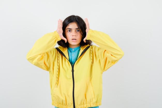 Mała dziewczynka trzymając się za ręce w pobliżu boków twarzy w koszuli, kurtce i patrząc zdziwiony. przedni widok.
