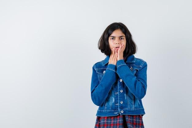 Mała dziewczynka trzymając się za ręce w pobliżu otwartych ust w koszuli, kurtce i patrząc zaskoczony. przedni widok.