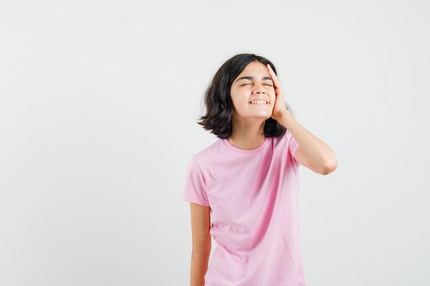 Mała dziewczynka trzymając się za rękę w twarz w różowej koszulce i patrząc wesoły, widok z przodu.