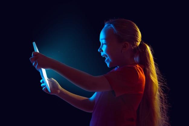 Mała dziewczynka trzymając tablet w ciemności