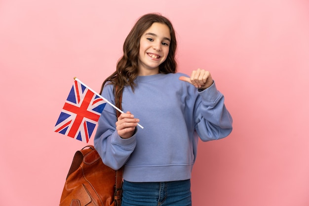 Mała dziewczynka trzymająca flagę wielkiej brytanii na białym tle na różowym tle dumna i zadowolona z siebie