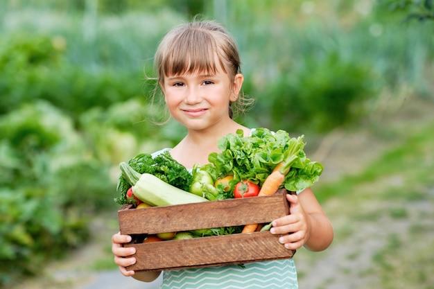Mała dziewczynka trzymająca kosz pełen organicznych warzyw i korzeni zbiorów na ekologicznej farmie ekologicznej. jesienne zbiory warzyw.